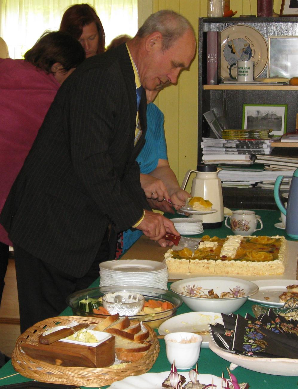 """Külavanem Romeo Mukk sünnipäevatorti lõikamas. Laua vasakus nurga on \""""Ergma sai \"""", mida esmakordselt küpsetati siis, kui Riigikogu esimees Ene Ergma 2007 Kuhjaveret külastas"""